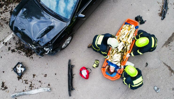 rescue workers attending to a car crash victim on a road