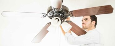 Ceiling fan being adjusted by handyman